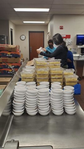 Staff prepare bags of chicken and dumplings for pick up
